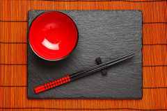 Two chopsticks and red plate on black stone background Stock Photography