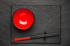 Two chopsticks and red plate on black stone background with copyspace Royalty Free Stock Image