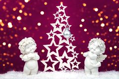 Free Two Christmas Baby Angels Statuettes On Snow With Christmas Tree Stock Image - 133435731