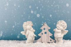 Two Christmas baby angels statuettes on snow with Christmas tree royalty free stock images