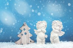 Two Christmas baby angels statuettes on snow with Christmas tree royalty free stock photography