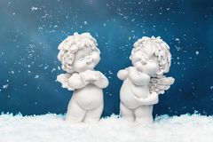 Two Christmas baby angels statuettes on snow at Christmas royalty free stock images