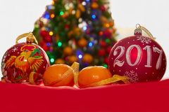 Two Christmas ball and tangerines. Two Christmas ball and mandarins on the Christmas tree Royalty Free Stock Photos
