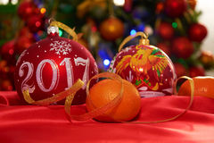 Two Christmas ball and tangerines. Two Christmas ball and mandarins on the Christmas tree Royalty Free Stock Photo