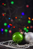 Two Christmas balls and beads with garland lights on colorful bo Stock Image