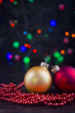 Two Christmas balls and beads with garland lights on colorful bo Stock Photo