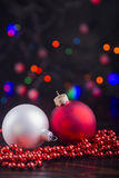 Two Christmas balls and beads with garland lights on colorful bo Royalty Free Stock Image