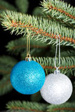 Two christmas balls hanging on a tree. Royalty Free Stock Photos
