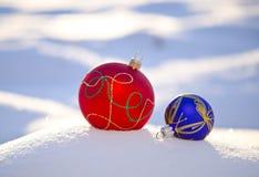 Two Christmas balls on winter fresh snow Stock Image