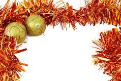 Two Christmas baubles with bright orange tinsel. Two yellow Christmas baubles with bright orange tinsel forming a frame on white backgound Stock Image