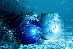 Two Christmas Baubles in Snow. Near Pine Tree Royalty Free Stock Photo