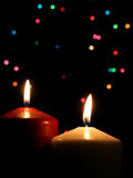 Two Christmas Candles. Up close, with festive lights in the background Royalty Free Stock Photo