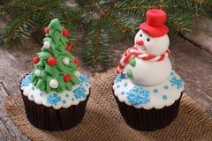 Two Christmas cupcake. Christmas tree and snowman on the table stock photo