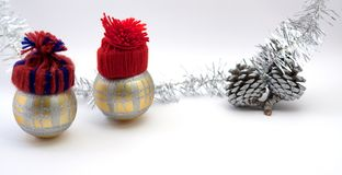 Two Christmas decoration balls with red handmade hats. Christmas decoration balls and pine cones. Blurred ribbon, soft white background Stock Image