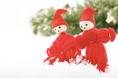 Two Christmas elves. A close-up of a two Christmas looking at something together while in a snowy, wintery environment with a green forest in the background Stock Photography