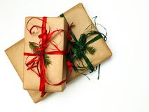 Two Christmas gift boxes packed in kraft and red and green ribbons on a white background stock photo