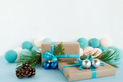 Christmas gift boxes wrapped of craft paper, blue and white ribbons, decorated of fir branches, Christmas balls and pine cones. Stock Images