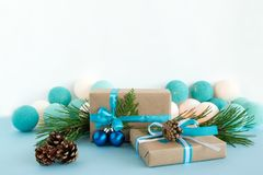 Christmas gift boxes wrapped of craft paper, blue and white ribbons, decorated of fir branches, pine cones and Christmas balls. Royalty Free Stock Photo