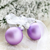 Two christmas ornaments. With ribbon and fir in background stock photos