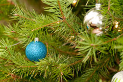 Two Christmas ornaments. Two different Christmas ornaments; sparkly blue sphere and silver shiny sphere Stock Photos