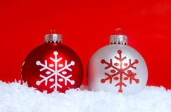 Two Christmas ornaments in snow Stock Images