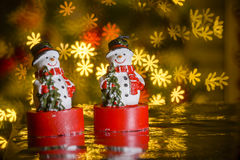 Two Christmas snowmen and flower shaped lights Stock Image