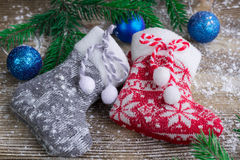 Two Christmas stockings on snowbound wooden background, blue bal Stock Photos