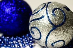 Two shiny Christmas balls with blue beads close up on white background royalty free stock photo