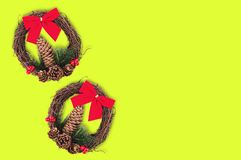 Two christmas wreaths with cone and twig of christmas tree and red textile bow and dry branches on yellow background with copy spa. Ce for your text royalty free stock image