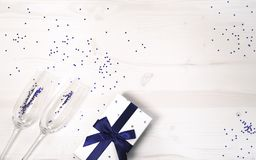 Two chrystal champagne glasses and a gift box tied with a blue ribbon on a white painted wooden table.  Celebration background.