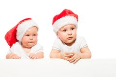 Two chubby babies wear red Christmas hats. Two chubby babies stand together and wear red Christmas hats on the white background royalty free stock image