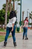 Two chubby girls with inline skates in the park. Happy royalty free stock photography