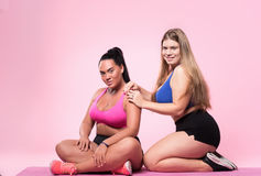 Two chubby women sitting on floor Royalty Free Stock Photography