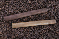 Two cigar on coffee. Beans background Royalty Free Stock Images