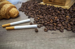 Two cigar, croissant and coffee beans on kitchen table. Close royalty free stock image