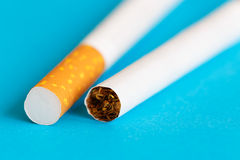 Two cigarettes on blue background Stock Photos
