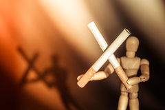 Two cigarettes in cross form holding by wooden man figure with blurred shadow on background Royalty Free Stock Photography