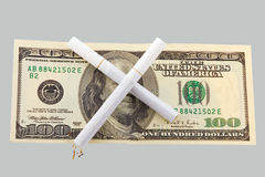 Two cigarettes crossed over one hundred dollar Royalty Free Stock Photos