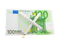 Two cigarettes crossed over one hundred euro. Bill saving money by quitting smoking Royalty Free Stock Images