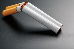 Two cigarettes in the form of a double-barreled shotgun on a black background with copy space. Stop smoking. The concept of. Smoking kills. Smoking as a deadly royalty free stock images