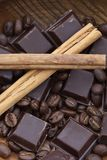Two cinnamon sticks, chocolate and coffee beans Stock Photography