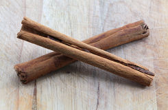 Two cinnamon sticks on a chopping board, crossed Royalty Free Stock Photos