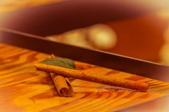 Two cinnamon sticks under soft lights. Two cinnamon sticks together with mint leaf displayed on wooden shelf under soft lights with blurred background Stock Images
