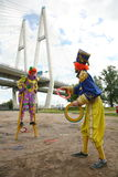 Two circus clowns animators throw colored rings Royalty Free Stock Photo