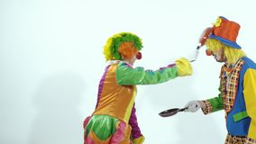 Two circus clowns playing with little frying pans stock video