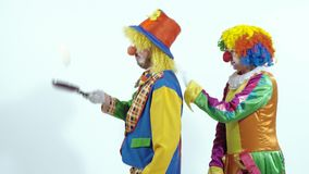 Two circus clowns throwing up a toy- pancake and catching it usin frying pans stock video footage