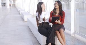 Two city women enjoying an informal meeting. Two city business women enjoying an informal meeting sitting outdoors in a long promenade discussing information on stock video footage