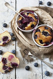 Two clafoutis with blueberries and cherries on ceramic ramekins and cake slices on rustic white vintage background Stock Image