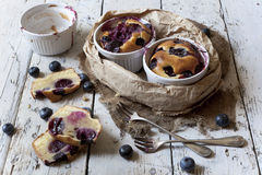 Two clafoutis with blueberries and cherries on ceramic ramekins and cake slices on rustic white vintage background Royalty Free Stock Image