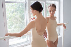 The two classic ballet dancers posing at barre Stock Image